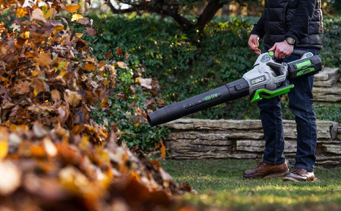 Man using the Power+ 650 CFM Blower to clear a lawn